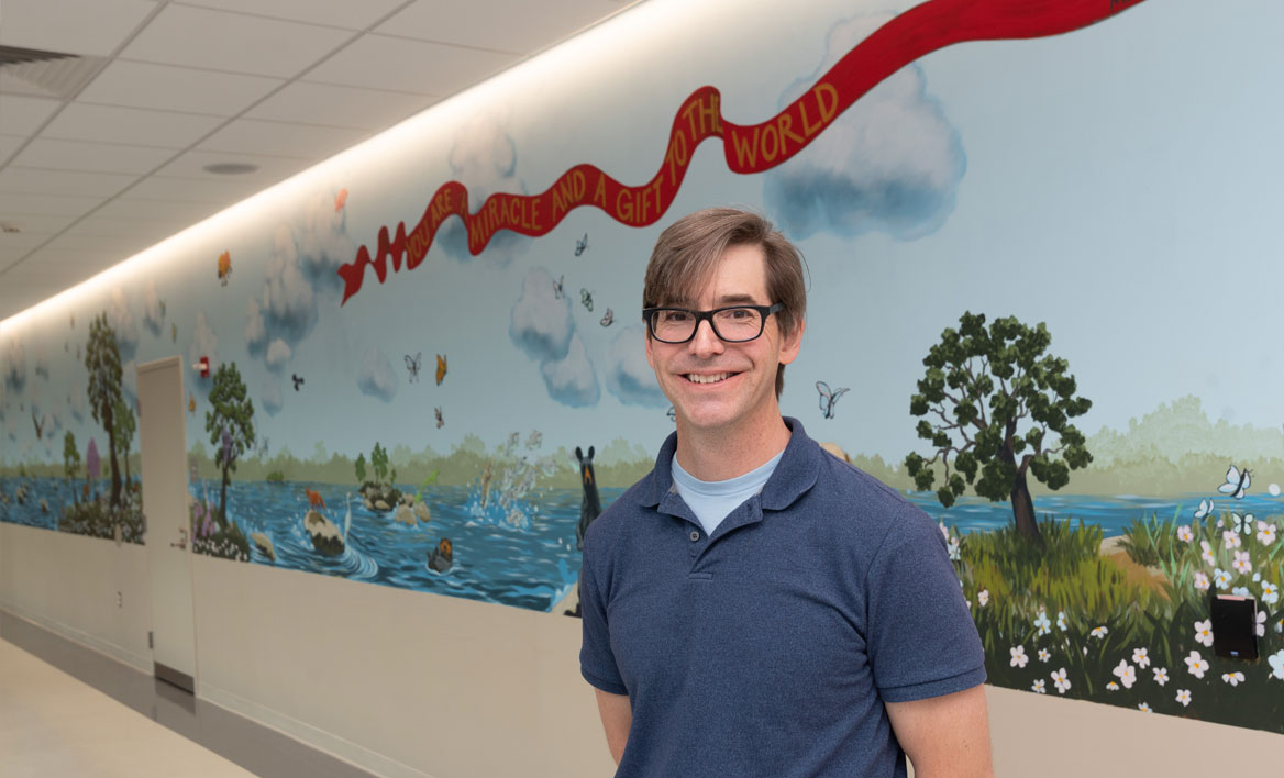 photo of alumnus Matt Lively and the mural he painted at the VTCC