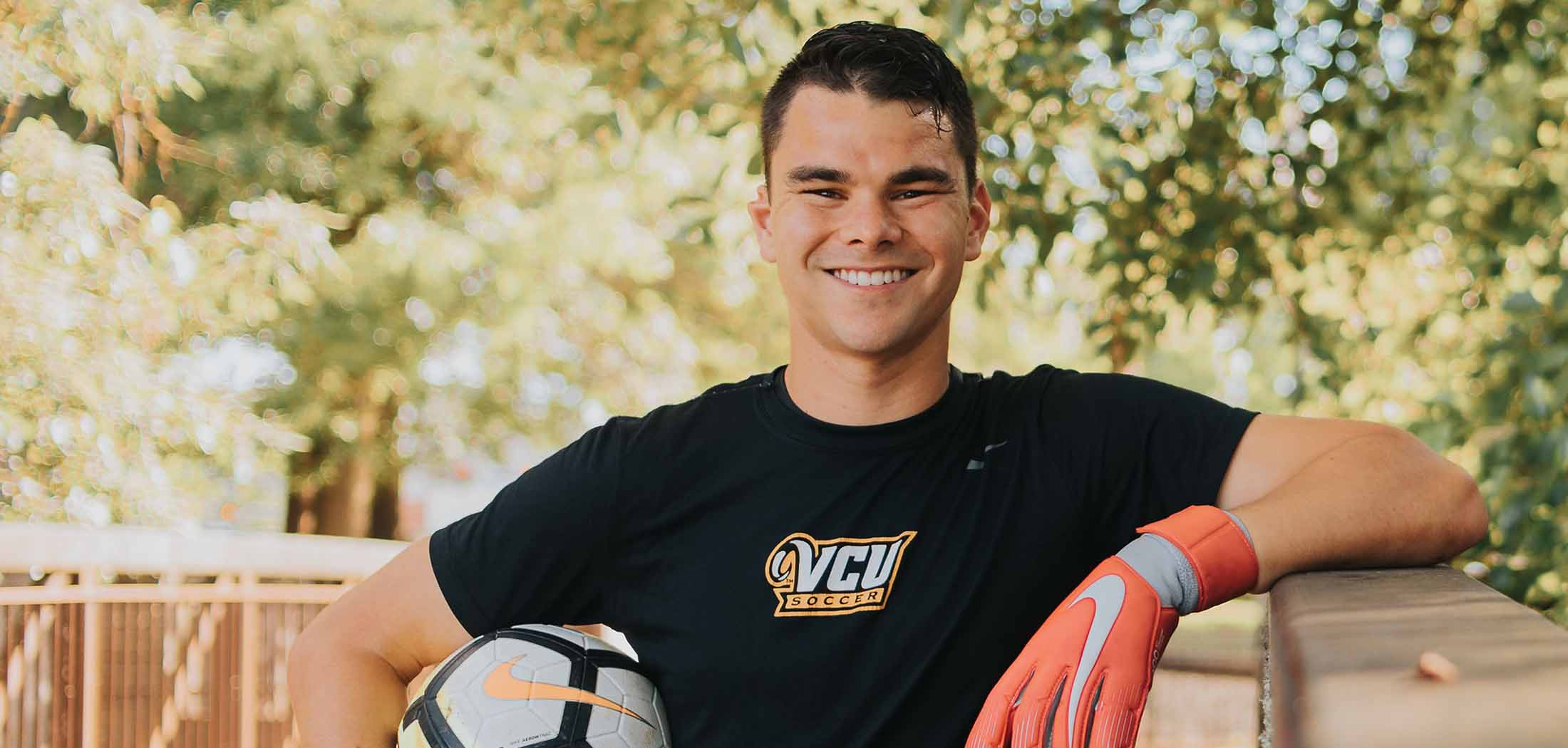 Mario wearing a VCU Soccer T-shirt and goalkeepr gloves. Holding a soccer ball at his side.